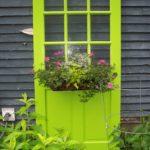 bright green door with flowers in garden