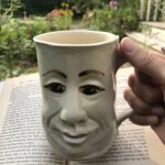 Coffee mug with man's face on it and an open book